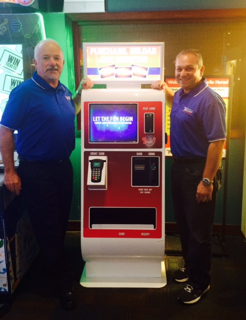 Debit card system fans Chuck Peitz (left) and Joe Ingui of Tricorp Amusements with an Embed system kiosk.